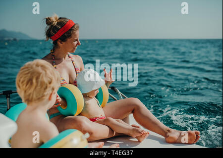 A mother and two small toddler children with armbands sitting on beach on summer holiday. - Stock Image