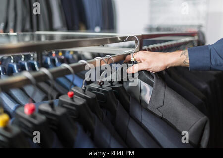 Man reaching for suit on hanger in menswear shop - Stock Image