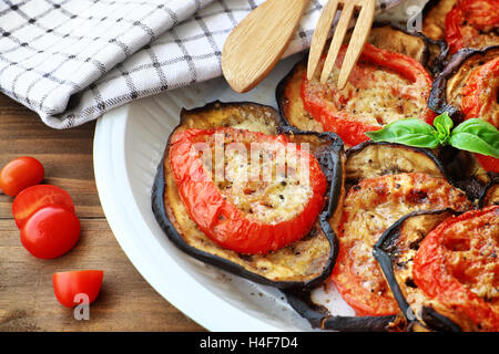 Tasty Thanksgiving meal, roasted aubergine with tomatoes and cheese on the plate on wooden table, delicious homemade - Stock Image