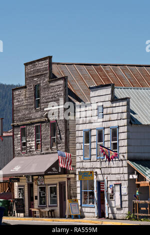 Old wooden buildings in the tiny village of Petersburg on Mitkof Island along the Wrangell Narrows in Frederick Sound with the Alaska Coast Range of mountains behind on Mitkof Island, Alaska. Petersburg settled by Norwegian immigrant Peter Buschmann is known as Little Norway due to the high percentage of people of Scandinavian origin. - Stock Image