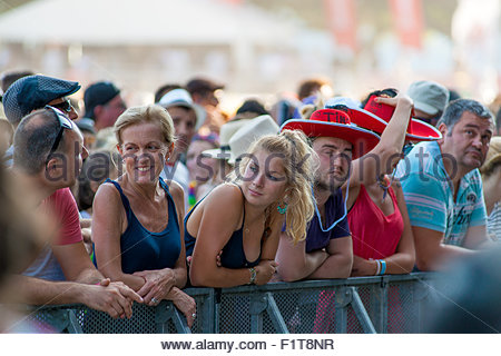 Concerts and festivals : mother and daughter making new friends while waiting for the band to appear on stage. - Stock Image
