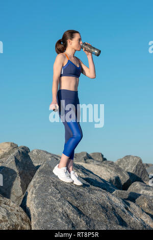 woman standing on rocks drinking water from a glass sports bottle after exercise - Stock Image