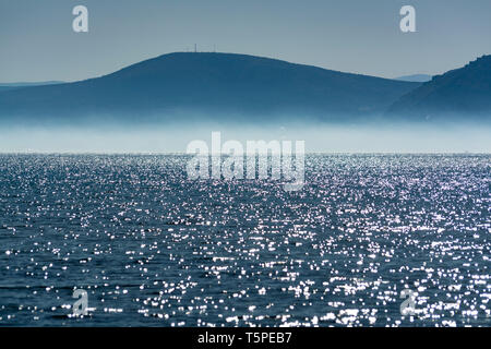 Seascape with low fog clouds over sea water in early morning with sun lights, nature background - Stock Image