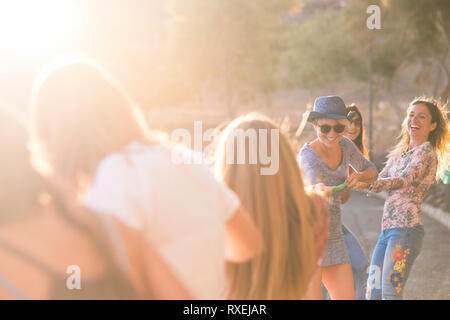 Group of young cheerful happy woman play with a cord all together for sumer leisure activity outdoor - playful and happiness concept having fun in fri - Stock Image