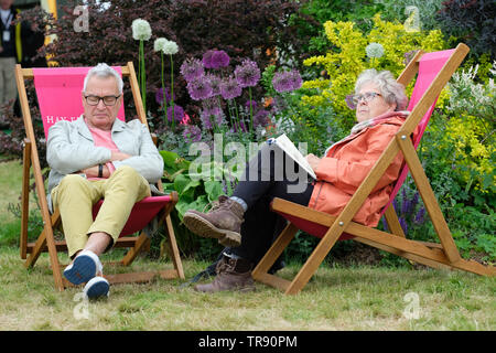 Hay Festival, Hay on Wye, Powys, Wales, UK - Friday 31st May 2019 - A visitor casts an eye on the weather as two visitors enjoy the chance to sit and rest in the deckchairs on the Festival lawns between events. Photo Steven May / Alamy Live News - Stock Image