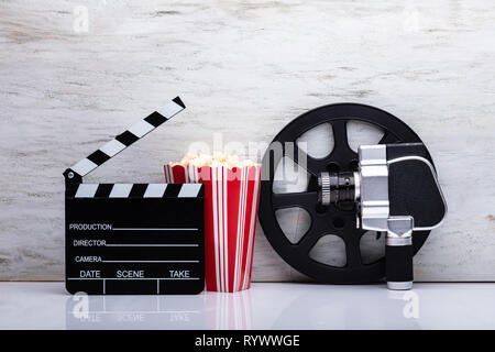 Close-up Of An Movie Camera With Popcorn And Clapper Board Against White Background - Stock Image