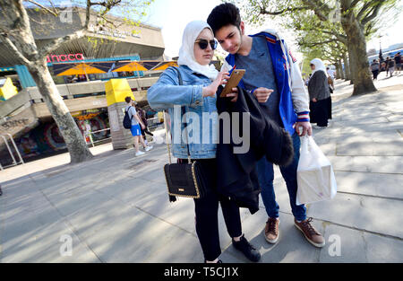 London, England, UK. Asian couple looking at a mobile phone by the Queen Elizabeth Hall, South Bank. - Stock Image
