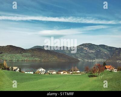 Green field, houses, lake, mountain and blue sky view - Stock Image
