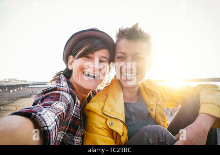 Happy gay couple taking selfie on the beach at sunset - Young lesbians having fun dating first time - Stock Image