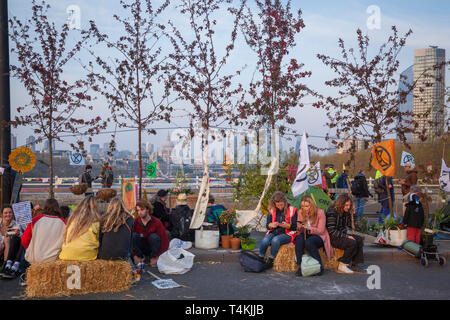 Protestors rest on Waterloo Bridge for the Extinction Rebellion demonstration with trees behind - Stock Image