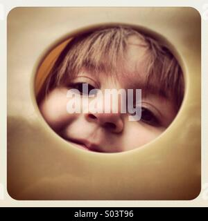 Toddler girl looking through a hole on a playground. - Stock Image