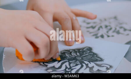 Woman hands painting wooden circle, close up - Stock Image