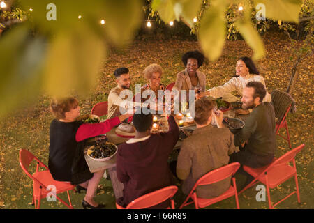 Friends toasting wine, enjoying dinner garden party - Stock Image