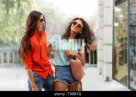 Two women in sunglasses walking on street happily - Stock Image