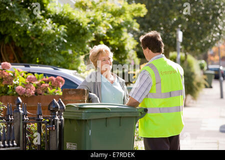 Woman talking to a council recycling man in the street about recycling household waste - Stock Image