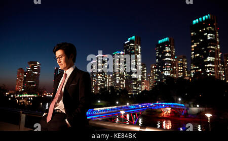 Businessman standing against night view of city - Stock Image