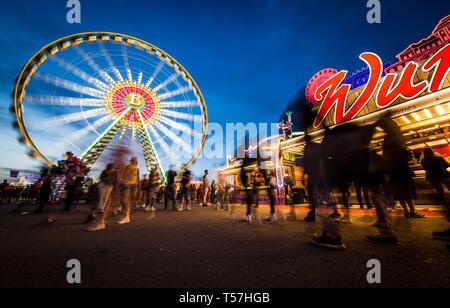 Stuttgart, Germany. 22nd Apr, 2019. Visitors enjoy the 81st Stuttgart Spring Festival at the Cannstatter Wasen at the blue hour. Credit: Christoph Schmidt/dpa/Alamy Live News - Stock Image