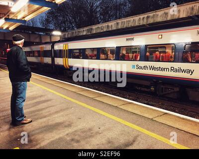 South Western Railways train at the platform of Sherborne train station, with a man standing on the platform waiting. Evening commuters. - Stock Image