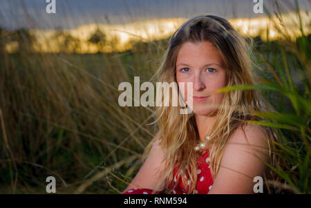 A portrait of a woman - aged 30 to 35 - in a field on a summers evening wearing a spotted red dress - Stock Image
