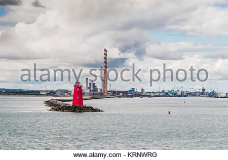 Poolbeg Lighthouse at the mouth of the River Liffey, with the chimneys of Pololbeg Generating Station and the Dublin - Stock Image