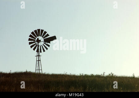 Silhouette of windmill in paddock, Queensland, Australia. Windmills are commonly used for pumping water from bores - Stock Image