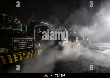 Line Of Dump Trucks Warming Up On A Cold Winter Morning, Pennsylvania, USA - Stock Image