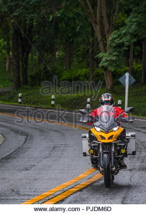 Biker on riding adventure bike on wet road, Nan, Thailand - Stock Image