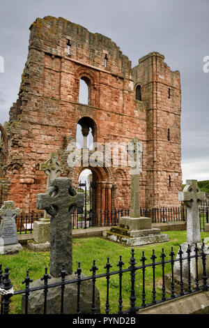Red stone front of Lindisfarne church ruins of the medieval priory with cemetery tombstones on Holy Island of Lindisfarne England UK - Stock Image