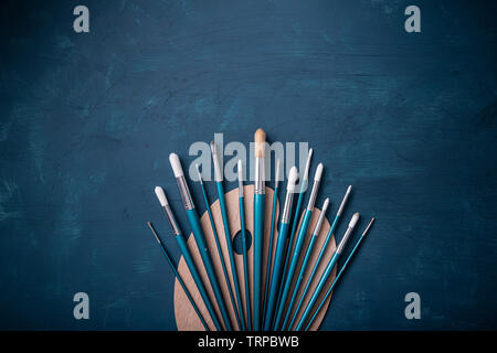 Top view of empty, new painters wooden palette with set of paint brushes - Stock Image