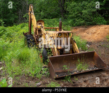 An old rusty yellow excavator parked in the forest Adirondack Mountains, NY USA - Stock Image