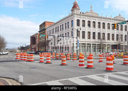 Orange stripe barrels in a road construction zone diverting traffic in downtown Montgomery Alabama, USA. - Stock Image