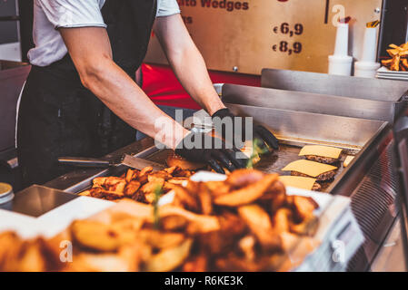 Process of cooking burgers at food truck on street. Fast food meal. Street food photography. - Stock Image