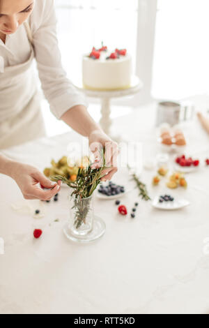 housewife using gorgeous greenery while preparing cake. close up cropped photo. the art of cooking - Stock Image