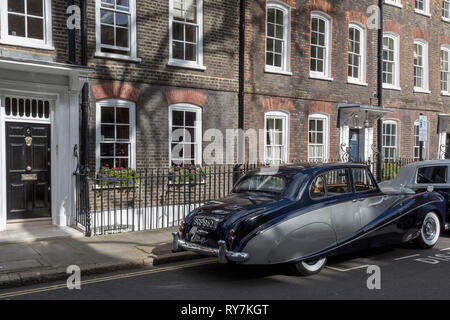 A 1964 Empress Bentley is parked in Smith Square, a small square behind the Houses of Parliament, before collecting their VIP passengers - barristers who are being sworn in as QCs (aka Silks in legal vernacular), on 11th March 2019, in London, England. - Stock Image
