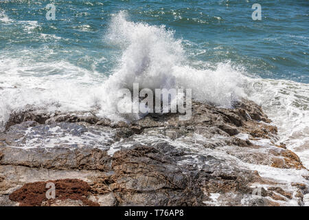 Ocean waves crashing on a rocky shore at Grand Fond in St Barts - Stock Image