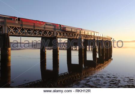 LNER train crossing Tay Rail Bridge reflected in River Tay at dusk Dundee Scotland  January 2019 - Stock Image