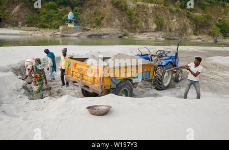 Manual worker loading sand on Tractor at River bank - Stock Image