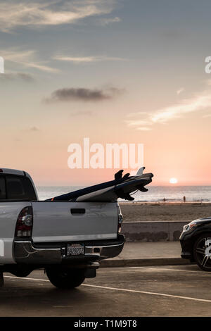 Surfboards in truck bed parked along beach at sunset, Newport Beach, California, USA - Stock Image