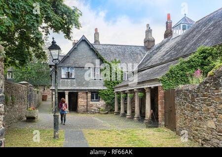 25 April 2018: Totnes, Devon, UK - The Guildhall, exterior. Woman walking through grounds. - Stock Image