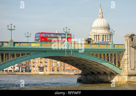Southwark bridge over the River Thames with a single red London double decker bus  and a view of St Paul's Cathedral - Stock Image