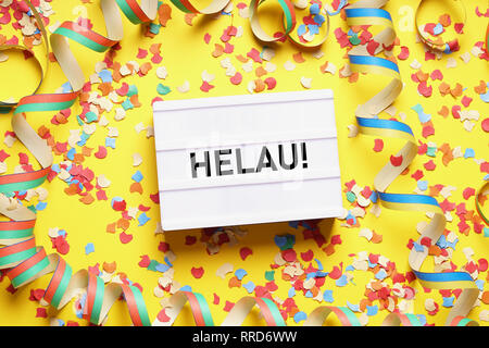 Helau is a traditional german fool's call used during carnival in Germany - flat lay with confetti and streamers - Stock Image