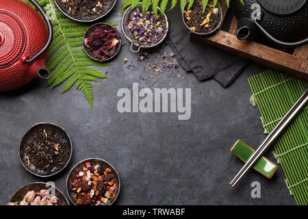 Set of different herbal and fruit dry teas on stone table. Top view flat lay with copy space - Stock Image