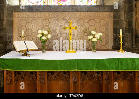 Altar with crucifix bible candles and flowers, church of Saint Andrew, Bramfield, Suffolk, England, UK - Stock Image