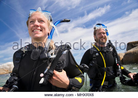 Portrait of happy scuba diver woman and man walking out of ocean after dive - Stock Image
