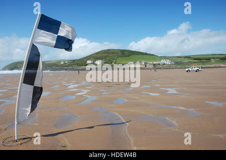 Black and white chequered RNLI beach safety flag flying on Croyde Bay beach with a RNLI lifeguard vehicle in the - Stock Image