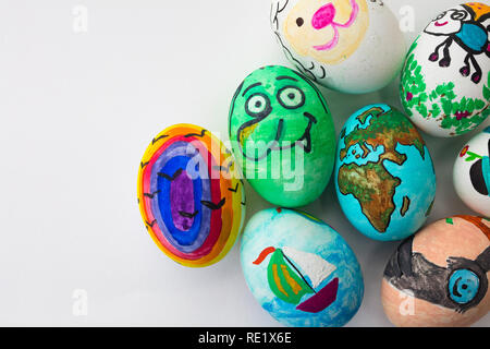 Detail of painted Easter eggs with different forms, cartoons and bright colors on isolated white background. - Stock Image
