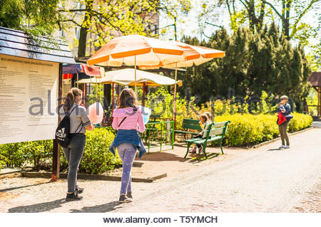 Poznan, Poland - April 18, 2019: Two girls with candyfloss walking on a footpath next to umbrellas in the old zoo on a warm spring season. - Stock Image