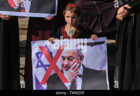 Palestinian kid holds a crossed-out placard depicting Israeli Prime Minister Benjamin Netanyahu during a protest at the Bahrain Peace Plan workshop in southern Gaza Strip. - Stock Image