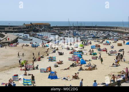 Lyme Regis, Dorset, UK.  27th June 2019. UK Weather.  Sunbathers flock to the beach at the seaside resort of Lyme Regis in Dorset to enjoy a day of clear blue skies and scorching sunshine.   Picture Credit: Graham Hunt/Alamy Live News - Stock Image
