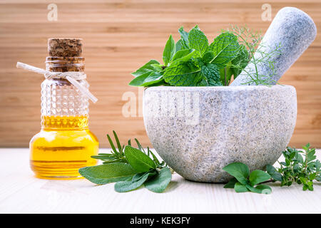 Alternative health care fresh herbs basil ,sage ,rosemary, mint and essential oil with mortar on wooden background. - Stock Image
